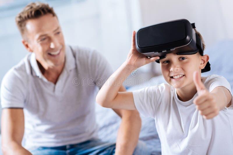 De gelukkige VR-hoofdtelefoon dragen en jongen die beduimelt omhoog tonen stock foto's