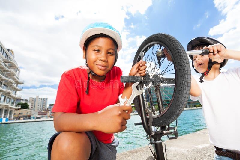 De gelukkige vrienden die fiets vervangen vermoeit in openlucht stock afbeeldingen