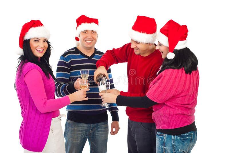 De gelukkige vrienden die van Kerstmis champagne gieten royalty-vrije stock afbeeldingen