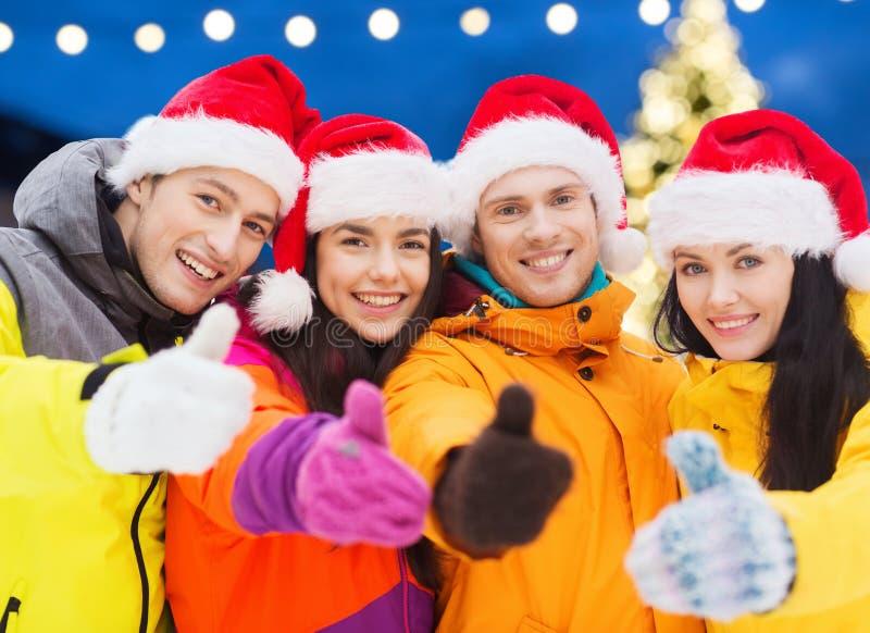 De gelukkige vrienden in santahoeden en ski past in openlucht aan royalty-vrije stock afbeeldingen