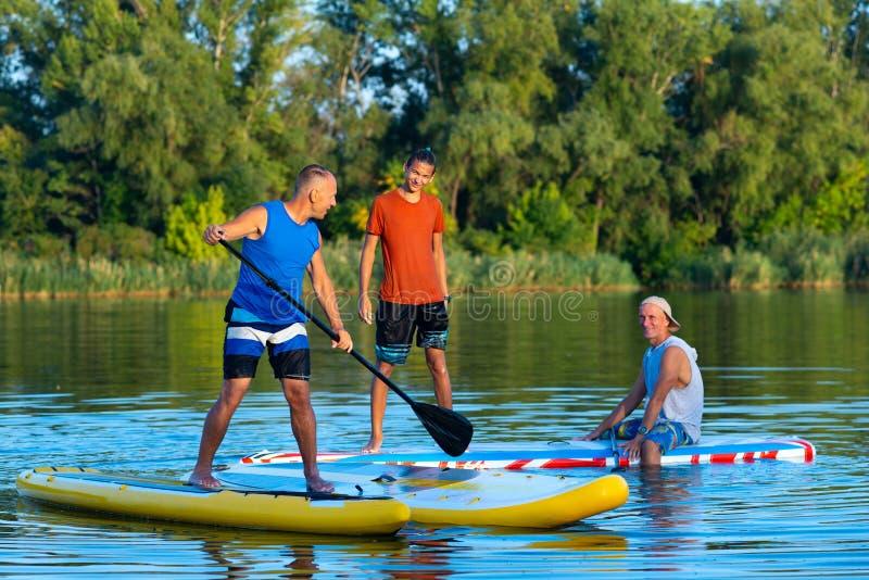 De gelukkige vrienden, SUP surfers communiceren en hebbend pret stock afbeeldingen