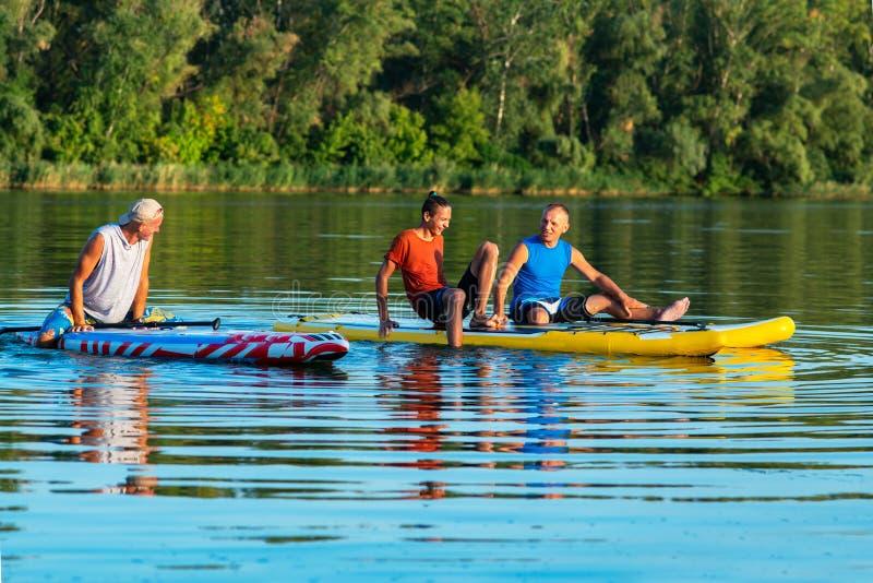 De gelukkige vrienden, SUP surfers ontspannen op de grote rivier tijdens sunse royalty-vrije stock afbeeldingen