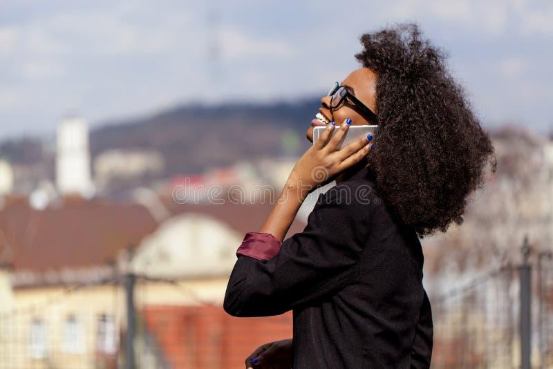 De gelukkige vrij Afrikaanse onderneemster in oogglazen glimlacht en spreekt de mobiele telefoon van o nthe bij de vage achtergro royalty-vrije stock foto's