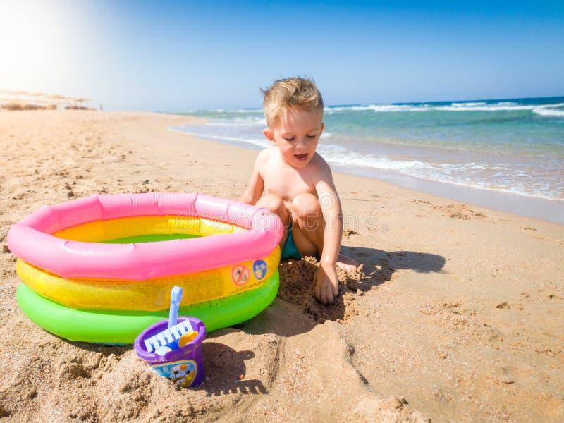 De gelukkige vrolijke toodlerjongen digigng schuurt op strand en het spelen met opblaasbaar zwembad En kind die ontspannen hebben stock afbeelding