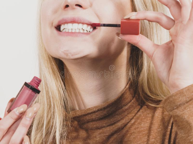 De gelukkige vrolijke vrouw die lippen gebruiken polijst royalty-vrije stock fotografie