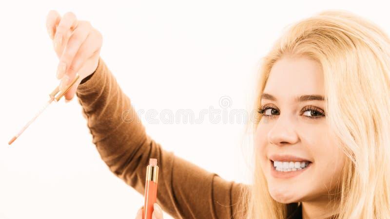 De gelukkige vrolijke vrouw die lippen gebruiken polijst stock foto's