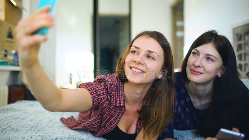 De gelukkige vrolijke zusters die selfie in ochtend maken en hebben pret thuis op bed in slaapkamer stock fotografie