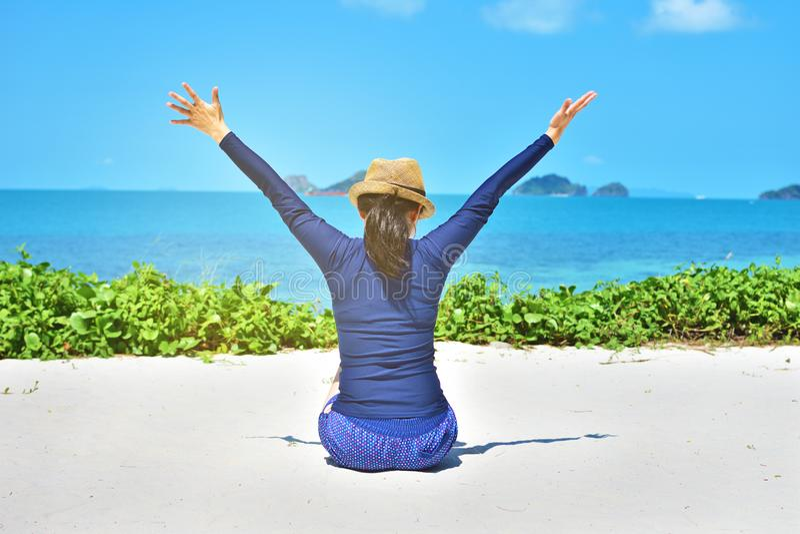 De gelukkige vrouw bewapent open het voelen vrijheidszitting op wit zand royalty-vrije stock fotografie