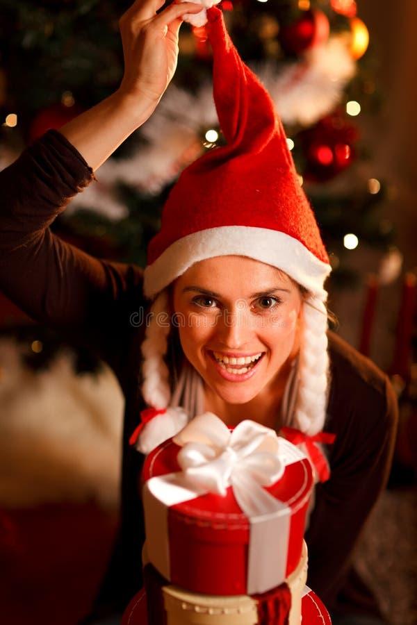 De gelukkige vrouw dichtbij Kerstboom met stelt voor stock foto's