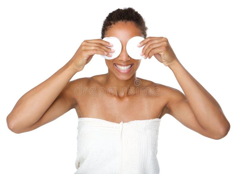 De gelukkige vrouw die ogen behandelen met maakt omhoog verwijderingsstootkussens stock foto's
