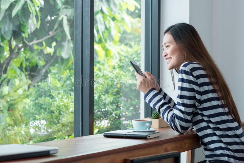 De gelukkige vrouw die van Azië mobiele het luisteren muziek gebruiken dichtbij venster bij caf stock afbeeldingen