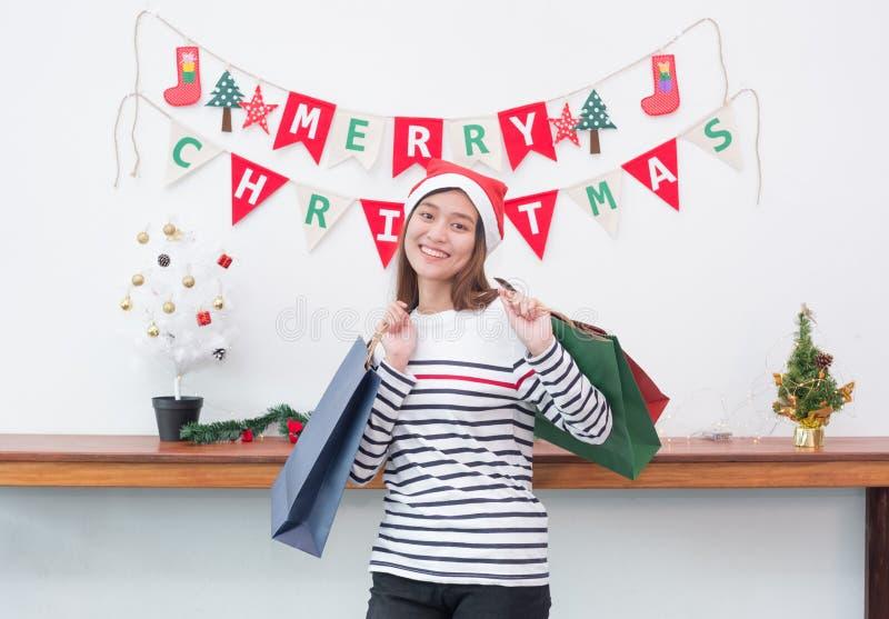 De gelukkige vrouw die van glimlachazië vele het winkelen zak in partij houden, koopt CH royalty-vrije stock foto's