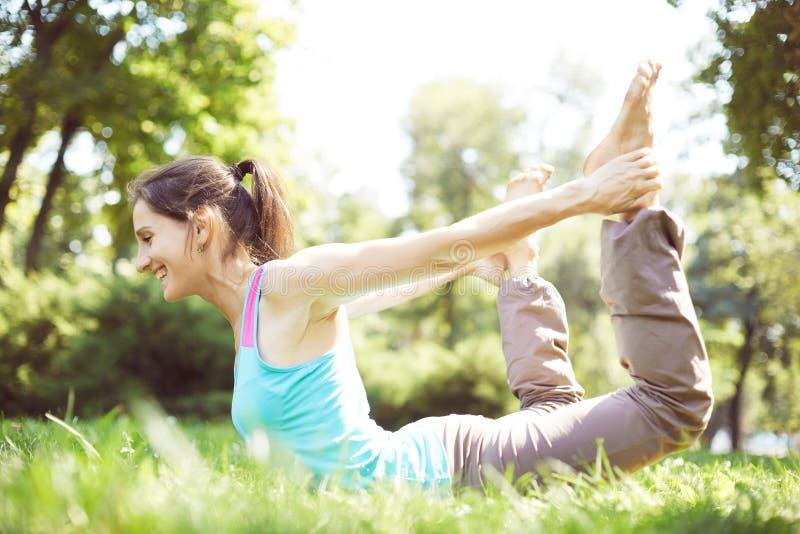De gelukkige vrouw die yogaoefeningen doen, mediteert in het park stock fotografie