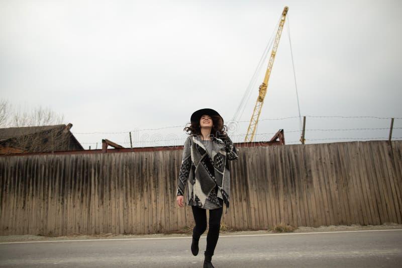 De gelukkige vrouw in een mooie grijze cardigan en de zwarte hoed hebben pret in het platteland royalty-vrije stock fotografie