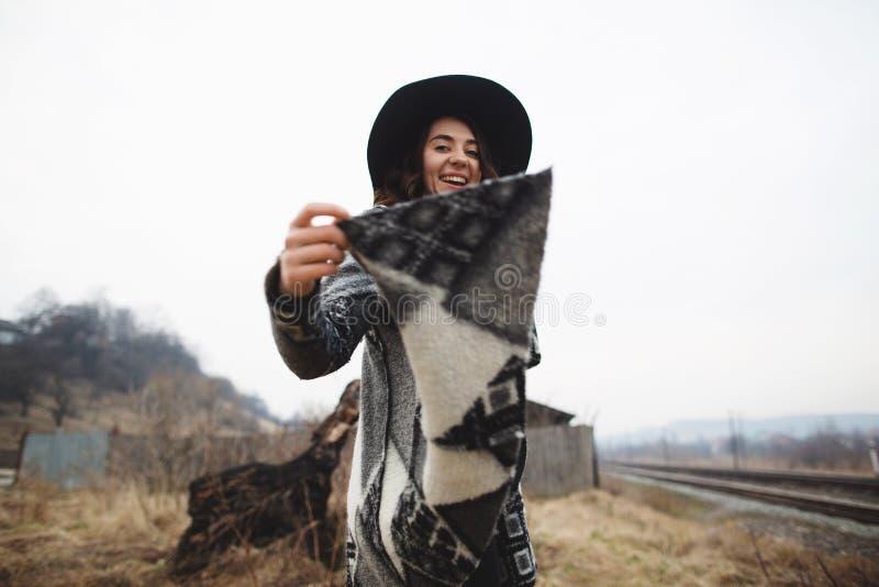De gelukkige vrouw in een mooie grijze cardigan en de zwarte hoed hebben pret in het platteland stock foto