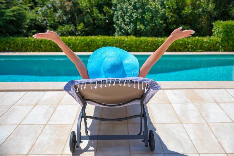 De gelukkige vrouw geniet van haar tijd van de de zomervakantie door de pool stock fotografie