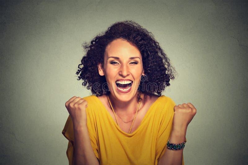 De gelukkige vrouw jubelt pompende extatische vuisten viert succes stock foto's