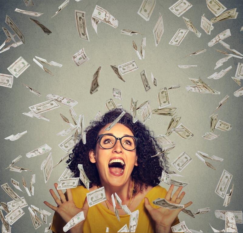 De gelukkige vrouw jubelt pompende extatische vuisten viert succes onder een geldregen stock afbeeldingen