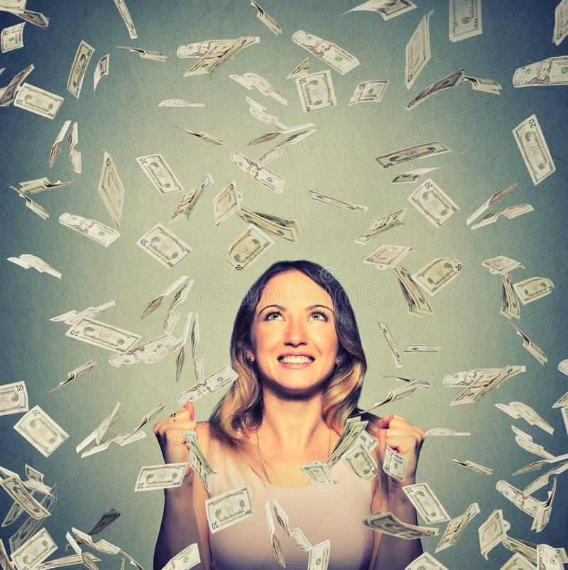 De gelukkige vrouw jubelt pompende extatische vuisten viert succes onder een geldregen stock afbeelding