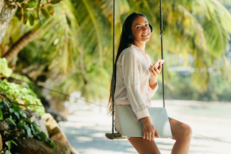 De gelukkige vrouw luistert aan muziek op strand en holdingslaptop stock afbeelding