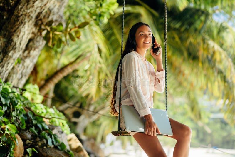De gelukkige vrouw luistert aan muziek op strand en holdingslaptop stock fotografie
