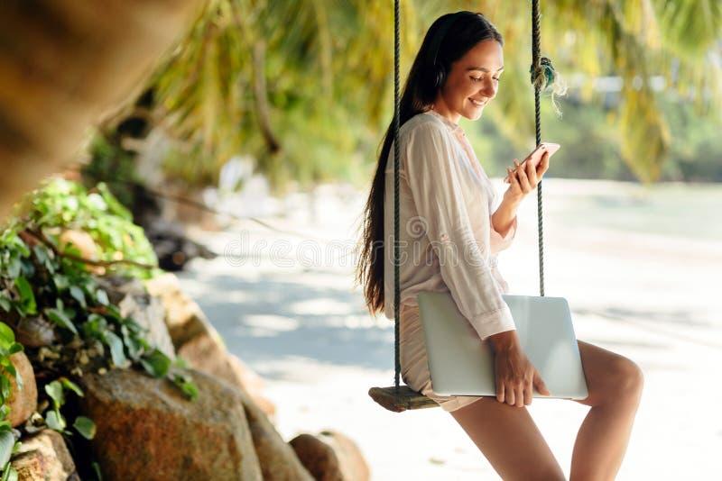 De gelukkige vrouw luistert aan muziek op strand en holdingslaptop stock foto's