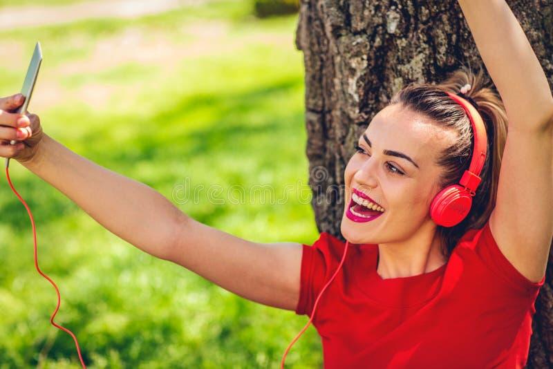 De gelukkige vrouw luistert aan muziek via hoofdtelefoons en smartphone openlucht royalty-vrije stock afbeelding