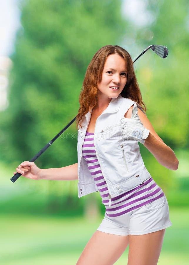 De gelukkige vrouw met een golfclub houdt een duim tegen royalty-vrije stock foto's