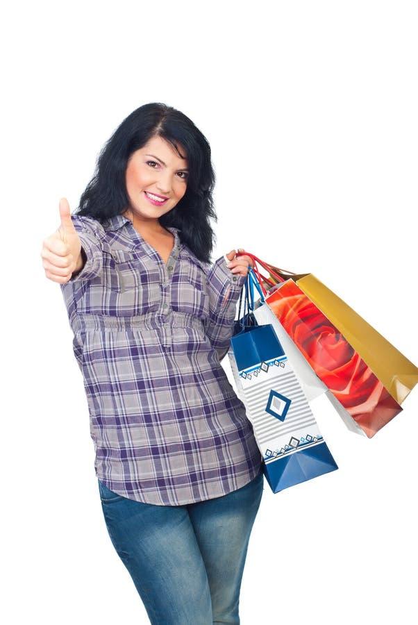 De gelukkige vrouw met het winkelen zakken geeft duimen stock foto's
