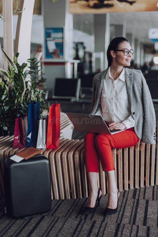 De gelukkige vrouw met notitieboekje wacht op vliegtuig royalty-vrije stock afbeelding