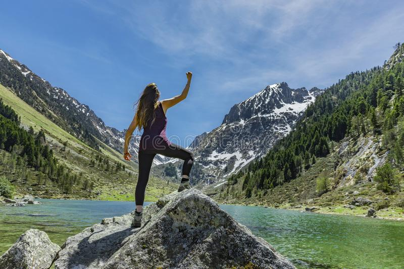De gelukkige Vrouw in overwinning stelt op een rots stock afbeeldingen