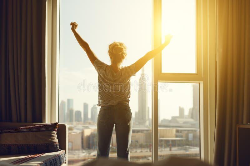 De gelukkige vrouw rekt en opent gordijnen bij venster in ochtend uit stock foto