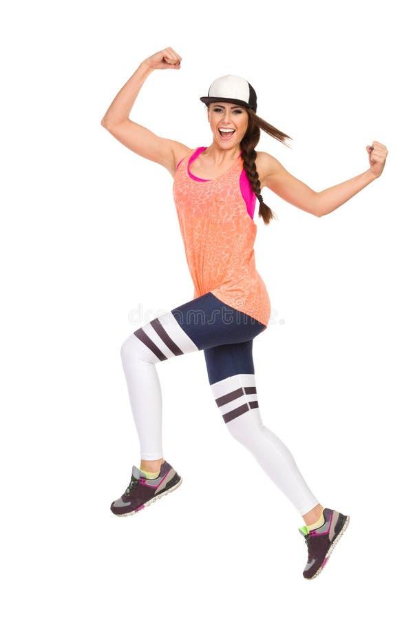 De gelukkige Vrouw in Sportenkleren springt en schreeuwt royalty-vrije stock foto's