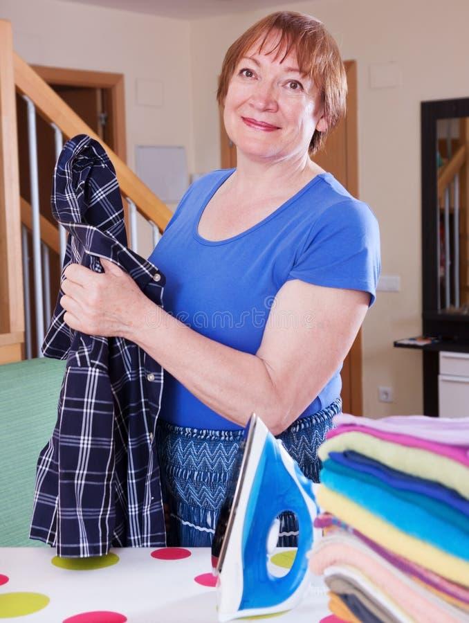 De gelukkige vrouw strijkt een overhemd stock foto's