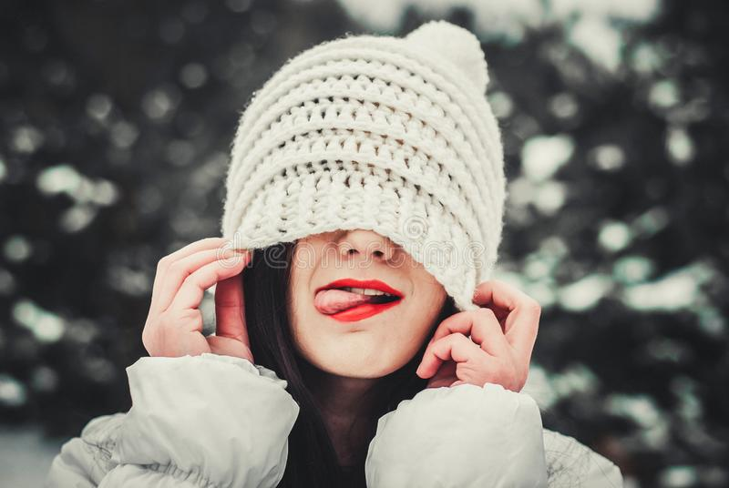 De gelukkige vrouw trekt een hoed op haar hoofd die een gebreide witte hoed dragen Het portret van de winter royalty-vrije stock foto's