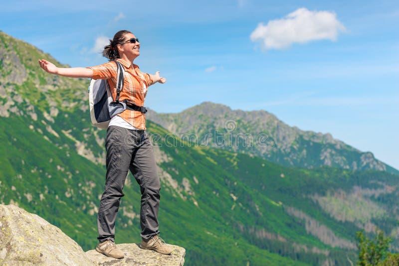 De gelukkige vrouw veroverde een hoge berg met een rugzak geniet van fre stock fotografie