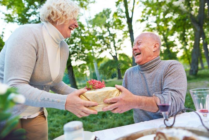 De gelukkige vrouw wenst de mens met gift geluk royalty-vrije stock foto's
