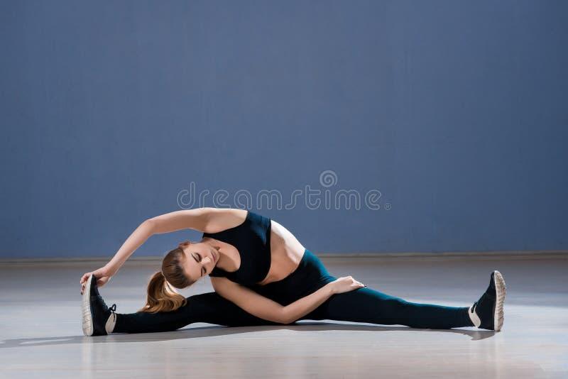 De gelukkige vrouw in yoga stelt in geschiktheidsstudio stock foto's