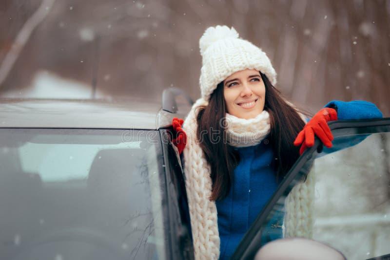 De gelukkige Vrouwelijke Auto die van Bestuurdersstanding by her de Sneeuw bewonderen royalty-vrije stock afbeeldingen