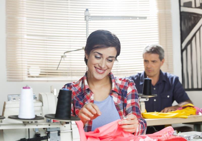 De gelukkige Vrouwelijke Fabriek van Kleermakersworking in sewing stock fotografie