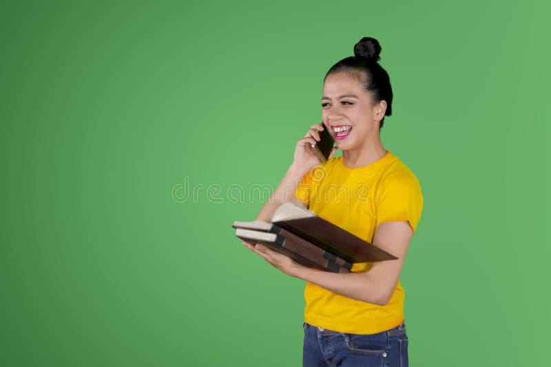 De gelukkige vrouwelijke student spreekt op de telefoon royalty-vrije stock foto