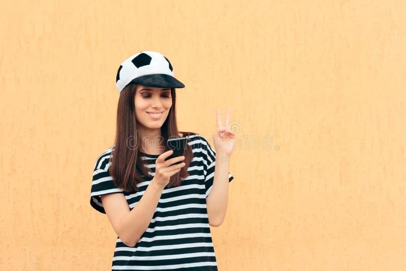 De gelukkige Vrouwelijke Ventilator die van de Voetbalvoetbal Smartphone controleren stock foto's
