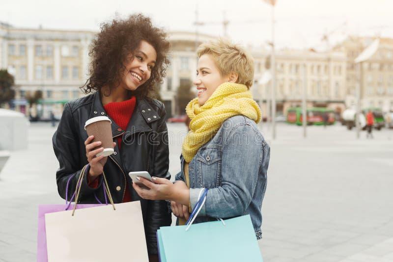 De gelukkige vrouwelijke vrienden met het winkelen doet in openlucht in zakken royalty-vrije stock fotografie