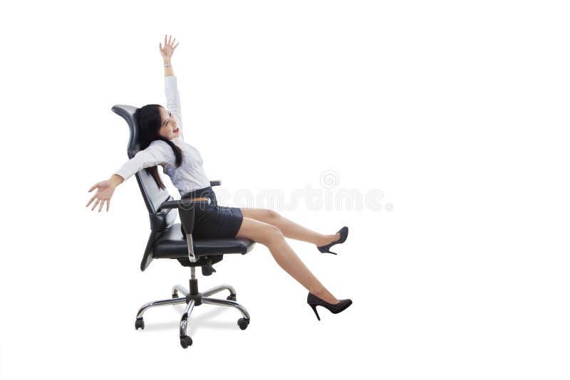 De gelukkige vrouwelijke werknemer zit op bureaustoel stock fotografie