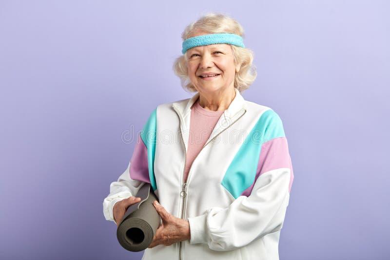 De gelukkige vrouwelijke de yogamat van de gepensioneerdeholding in handen, komt aan yogaklasse in studio royalty-vrije stock afbeelding