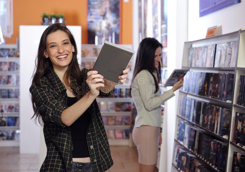 De gelukkige vrouwen bij de videohuur slaan op stock afbeelding
