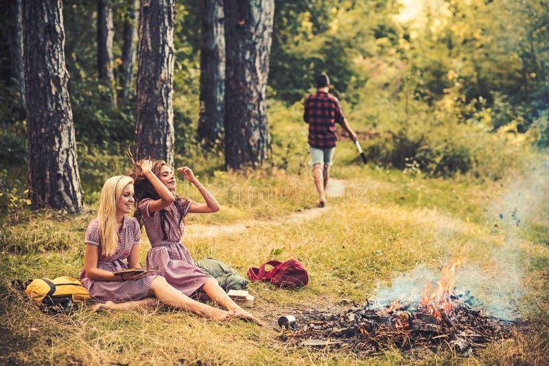 De gelukkige vrouwen met de vage mens in vrouwen van de de zomer de bosmanier in retro kleding ontspannen bij vuur Schoonheidsmei royalty-vrije stock fotografie
