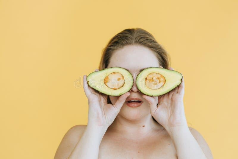 De gelukkige vrouwenholding sneed vers avocado's over haar ogen stock foto's