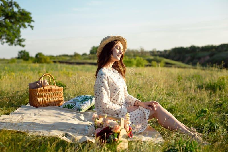De gelukkige VrouwenLevensstijl, mooi ontspannen meisje in een strohoed op de mand van de aardpicknick bloeit in de stralen van stock afbeeldingen