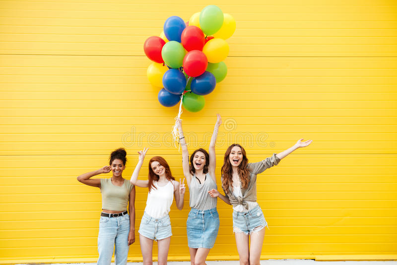 De gelukkige vrouwenvrienden hebben pret met ballons stock afbeeldingen